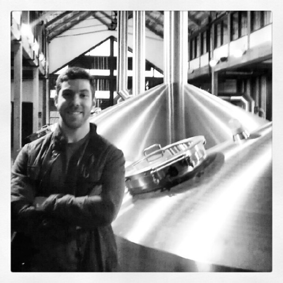 Happy homebrew husband next to a huge vat of cooking beer at New Belgium Brewery.